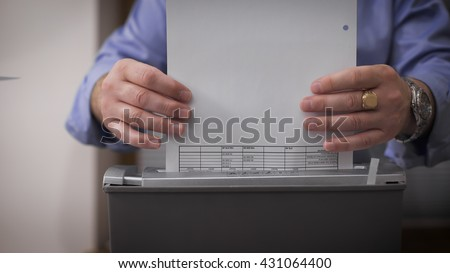 Close-up of male hands destroy documents. Female hands serving reports for destruction. Financial crime - stock photo
