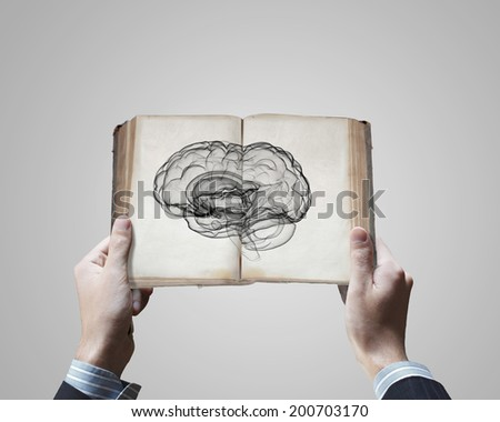 Close up of male hands holding opened book with brain picture - stock photo