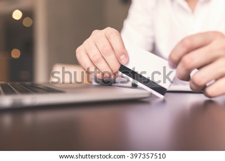 Close up of male hands making online payment. Selective focus, depth of field - stock photo