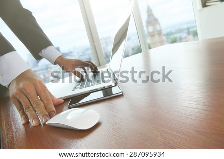 Close up of male hands on mouse and over black keyboard of laptop during typing with lon?on city blurred background - stock photo