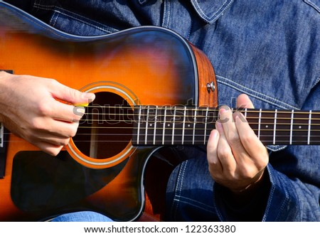 Close up of male hands playing guitar - stock photo