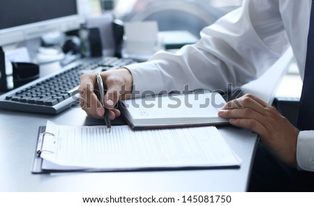 Close-up of male hands pointing at business document - stock photo