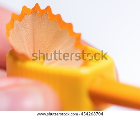 Close up of male hands sharpening a pencil on white background - stock photo
