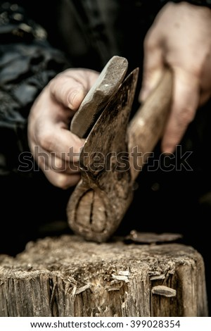 Close-up of male hands sharpening dirty old rusty axe with a grindstone on tree stump