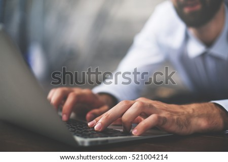 Close up of male hands typing on laptop keyboard