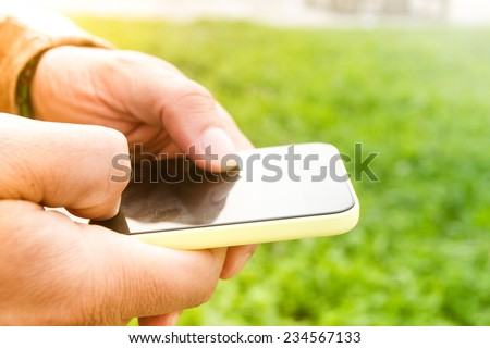Close-up of male hands using a smart phone, in a park