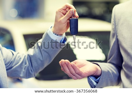 close up of male hands with car key in auto salon - stock photo