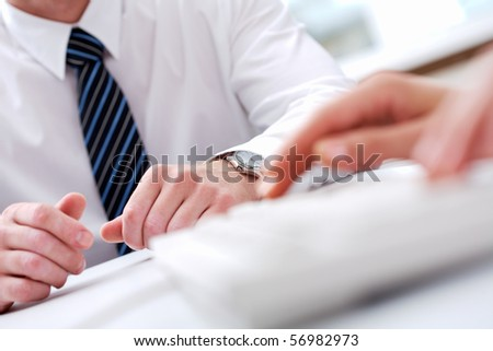 Close-up of male hands with typing secretary hands in front of him - stock photo