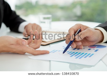 Close-up of male hands working with diagrams at office - stock photo