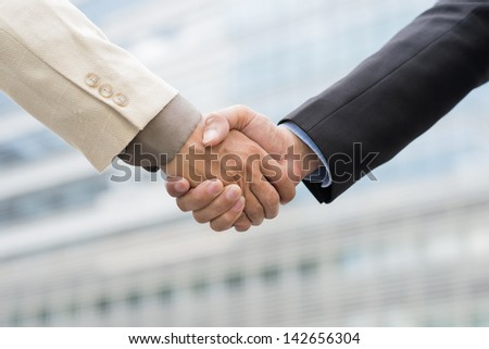 Close-up of male handshaking outside - stock photo