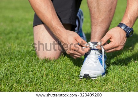 Close up of male legs kneeling. The athlete ties the laces on green grass  - stock photo