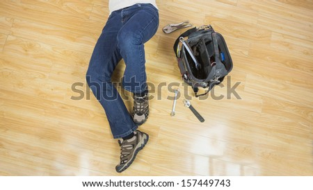 Close up of male legs lying on floor next to tools in bright room