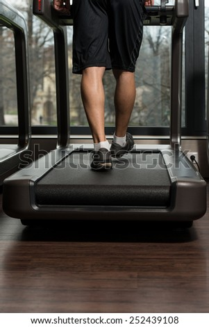 Close Up Of Male Legs Running On Treadmill - Blurred Motion - stock photo
