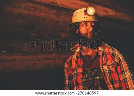 Close Up of Male Miner Wearing Lit Safety Helmet Lamp and Plaid Shirt Leaning Against Wooden Wall and Looking to the Side in Warm Yellow Light
