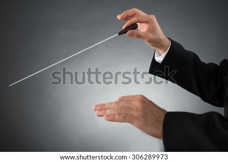 Close-up Of Male Orchestra Conductor Hands Holding Baton