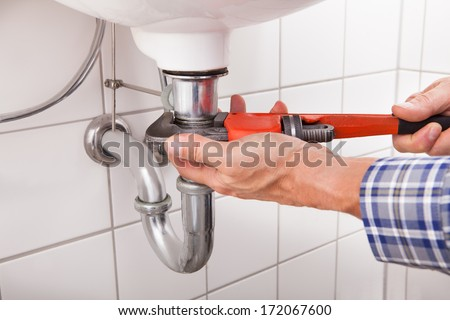 Close-up Of Male Plumber Fitting Sink Pipe In Bathroom