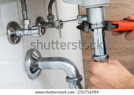 Close-up Of Male Plumber Fixing Sink In Bathroom - stock photo