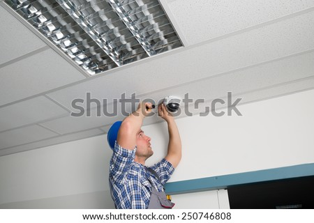 Close-up Of Male Technician Adjusting Cctv Camera On Ceiling - stock photo