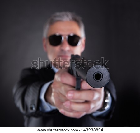 Close-up Of Male With Handgun Over Black Background - stock photo