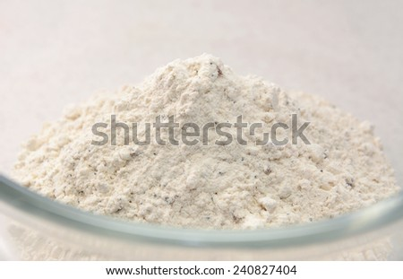 Close-up of malted, mixed seed bread flour mix in a glass bowl - stock photo