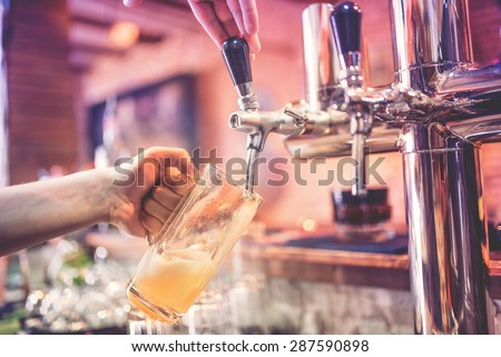 close-up of man, barman hand at beer tap pouring a draught lager beer at restaurant, pub or bistro - stock photo