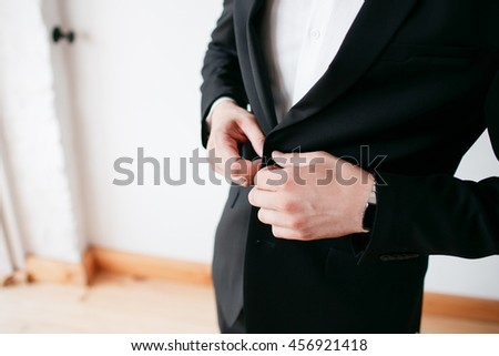 Close-up of man buttoning his suit jacket while standing against white background