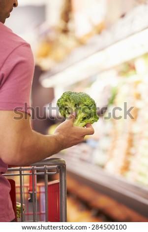 Close Up Of Man Choosing Broccoli In Supermarket - stock photo