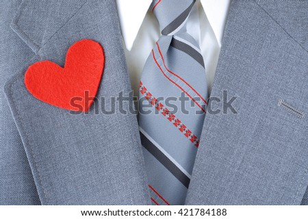 Close up of man dressed in a suit jacket in grey with red, black and grey striped tie and a white shirt. Heart shaped felt cutouts on the lapels indicate love for Dad, great for Fathers Day - stock photo