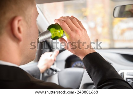 Close-up Of Man Drinking Beer While Driving Car - stock photo