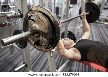 close up of man flexing biceps with barbell in gym