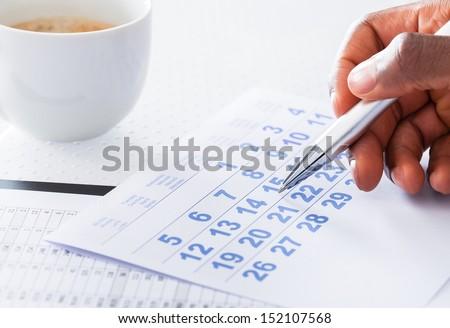 Close-up Of Man Hand Holding Pen On Calendar - stock photo