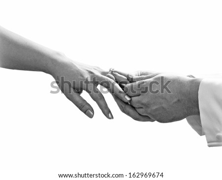 Close up of man hand putting a wedding ring on the bride finger isolate on white background, Black and white photography - stock photo
