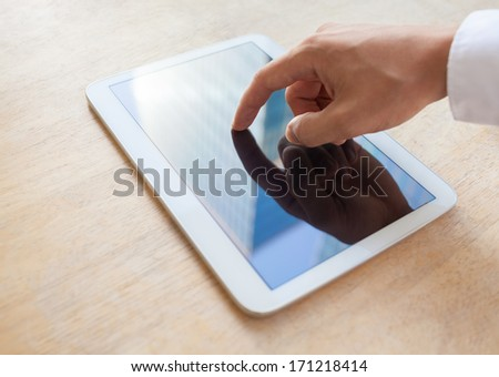 Close up of man hand touching digital tablet