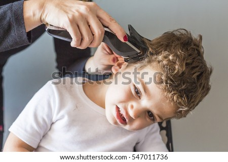 Close-up of man hands grooming kid boy hair at home