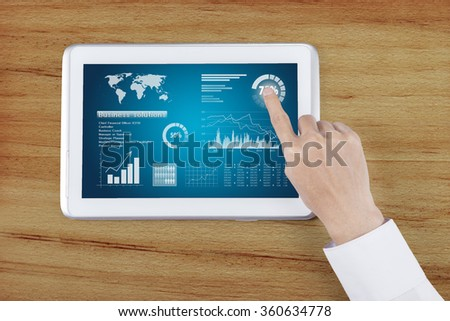 Close up of man hands holding the digital tablet with business chart on a screen - stock photo