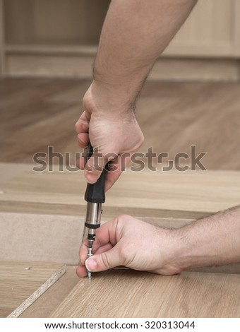Close-up of man hands with a screwdriver