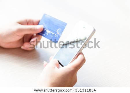 Close-up of man hands with smartphone and credit card as online shopping or online payment concept. Selective and shallow focus.