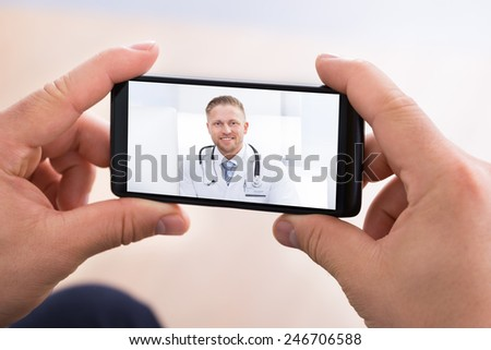 Close-up Of Man Having Video Chat With Doctor On Smartphone - stock photo