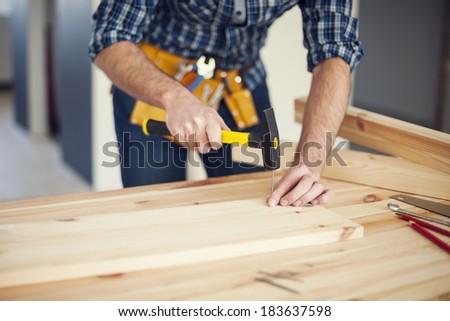 Close up of man hitting nail by hammer  - stock photo