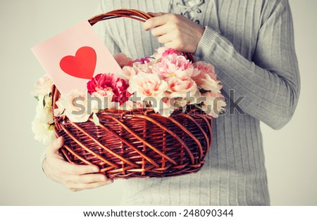close up of man holding basket full of flowers and postcard. - stock photo