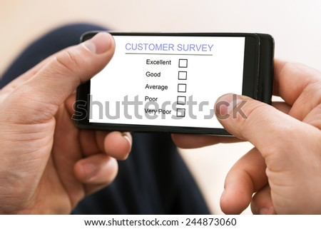 Close-up Of Man Holding Mobile Phone Showing Customer Survey Form - stock photo