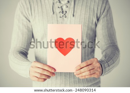 close up of man holding postcard with heart shape. - stock photo