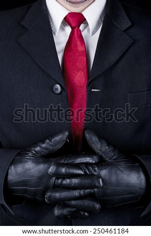 Close up of man in black suit, red tie and leather gloves. - stock photo