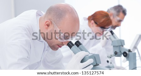 close-up of man in chemistry lab analyzing under microscope and another three researchers on the background - stock photo