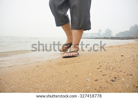 Close up of man in short walking alone at tropical exotic beach with blue ocean wearing flip flops                             - stock photo