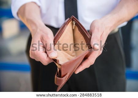 Close-up of man in suit holding empty purse. - stock photo