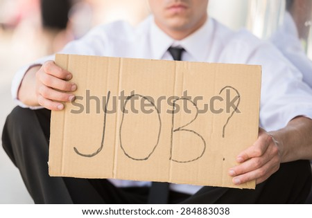 Close-up of man in suit holding sign in hands. Unemployed man looking for job. - stock photo