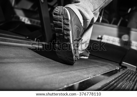 Close-up of man legs running by treadmill in sports club , black and white photography - stock photo