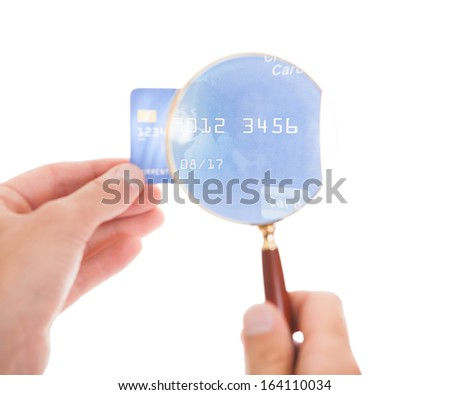 Close-up Of Man Looking At Credit Card Through Magnifying Glass On White Background - stock photo