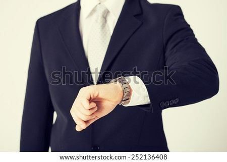 close up of man looking at wristwatch. - stock photo